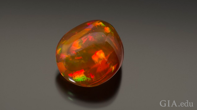 A polished gem with orange and green flashes of color.