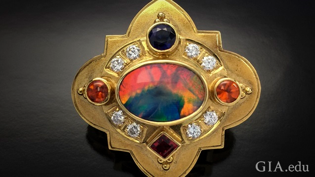 An orange, blue and green stone is the center piece of this shield-like brooch. The center stone is framed by diamonds, orange, blue and red gems.