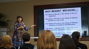 Woman stands in front of audience next to projected slide that reads: Why Beads? Because …