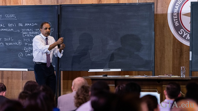 A man talks in front of a blackboard in a classroom-like setting.