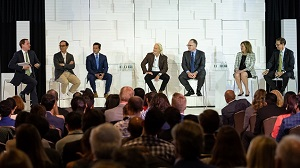 A panel of seven people sit on the stage to discuss issues.