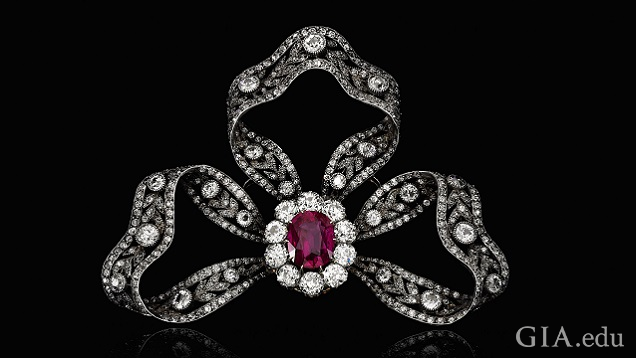 Three loops of diamond ribbons form a bow around a ruby framed by more diamonds.