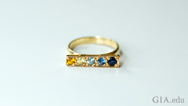 A gold rectangular base on the top of the ring holds a citrine and Montana sapphires.