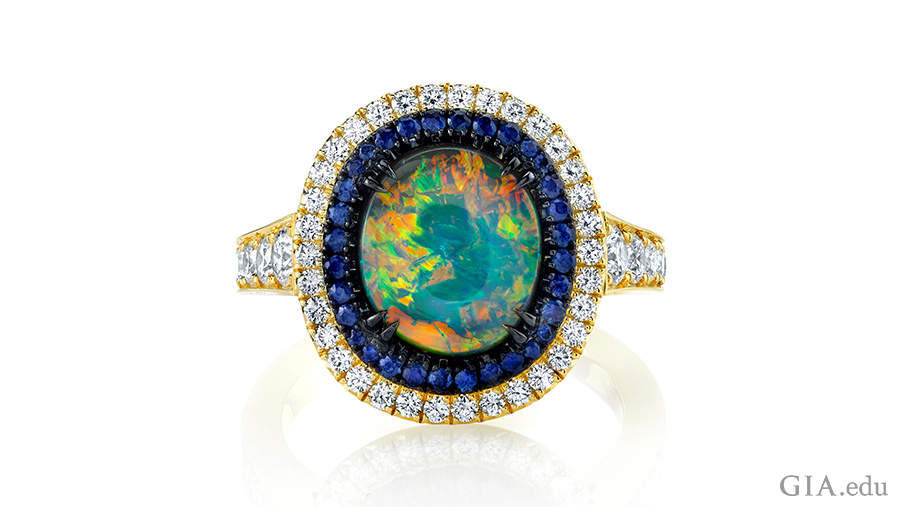 Sapphires and diamonds encircle the October birthstone, a 1.92 carat black opal in a stunning 18K yellow gold and black rhodium ring.