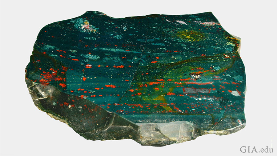 A giant slab of the March birthstone, bloodstone, is green with red, yellow, and white spots.