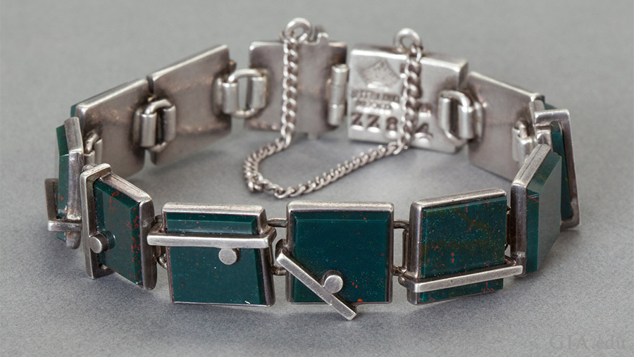 A rare Mexican silver bracelet featuring the March birthstone has bezel set bloodstones in silver, bar and ball overlay links, and is secured with a box clasp and chain.