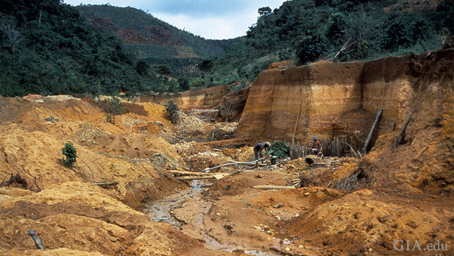 Landscape of a carved out mining ditch with a small stream running through, surrounded by tree-covered mountains in Brazil where the June birthstone, alexandrite, is found.
