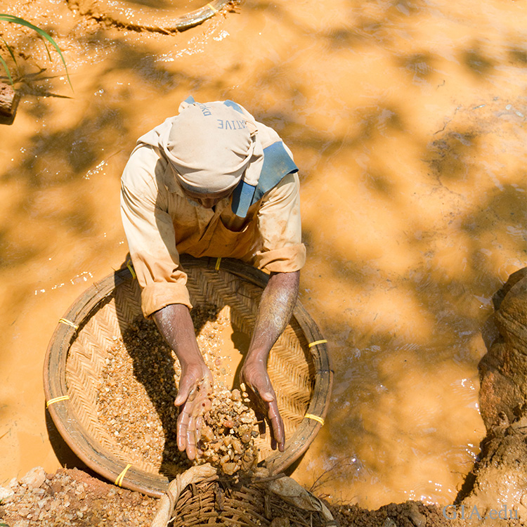 Using the same rudimentary washing techniques as generations before them in Sri Lanka, a miner is searching for sapphire among the gravels in a local stream. Courtesy: Afsaneh Tazari