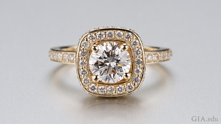 A gold ring designed from a CAD model features the April birthstone with a round center diamond surrounded by small diamonds and a diamond band.