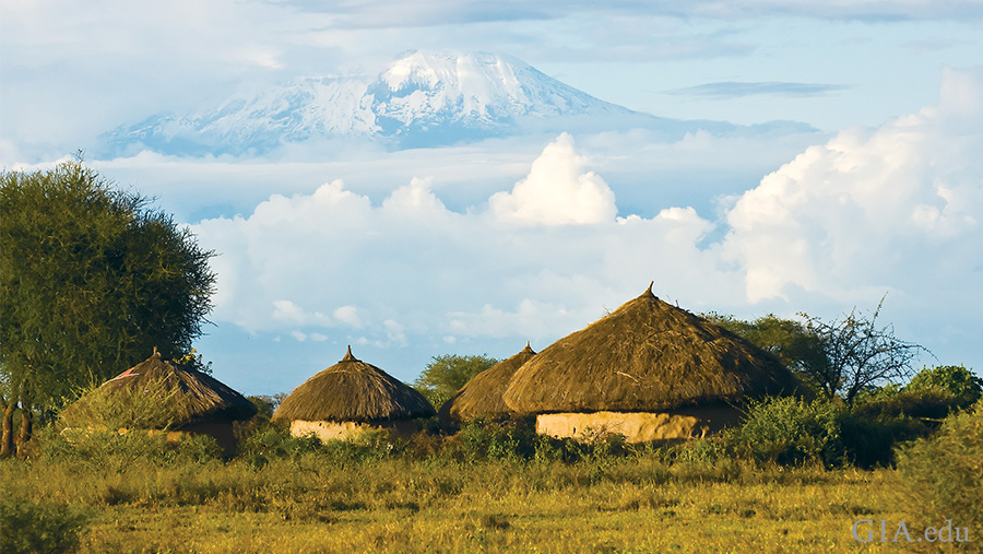Landscape of huts in a field with the summit of Mount Kilimanjaro emerging from the clouds in the distance, where the December birthstone tanzanite is mined.