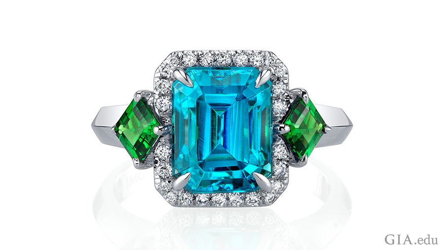 Handcrafted December birthstone ring with a 6.59 carat emerald cut blue zircon center stone accented by emerald cut tsavorite garnets, and brilliant diamond rounds set in 18K white gold.
