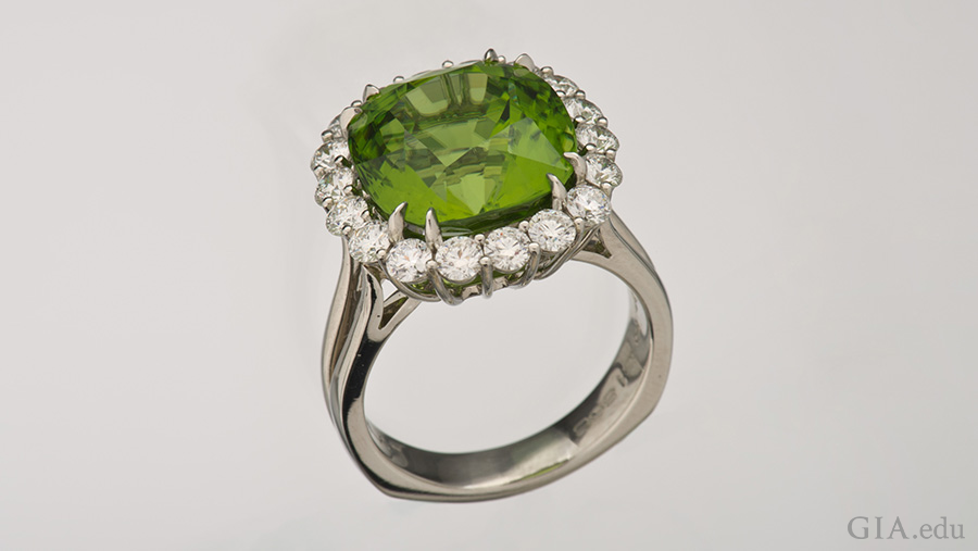 The 10.89 ct peridot in this platinum ring is surrounded by a halo of diamonds. Photo: Robert Weldon/GIA. Courtesy: Richard Krementz Gemstones