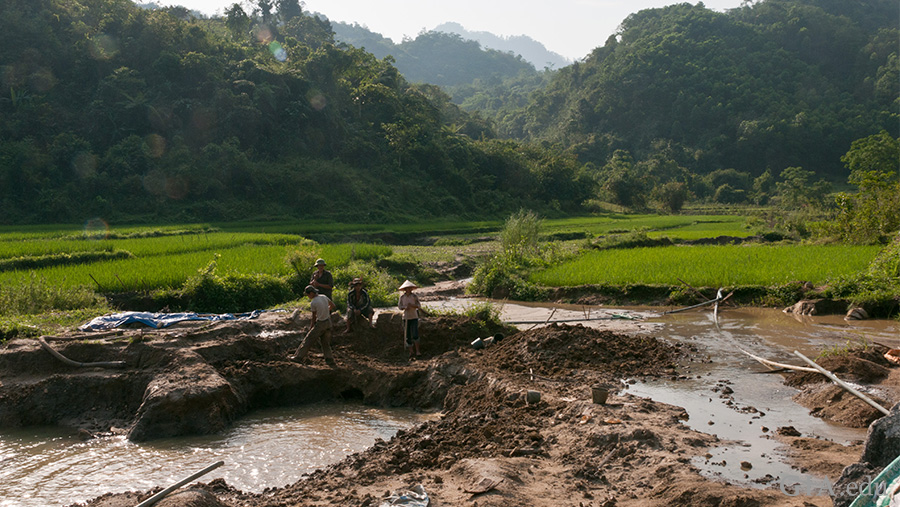 In this scene from Vietnam's Luc Yen region, a ruby and spinel mining operation can be seen in the foreground, with rice paddies rolling behind it against a background of craggy mountains cloaked in trees. Photo: Vincent Pardieu