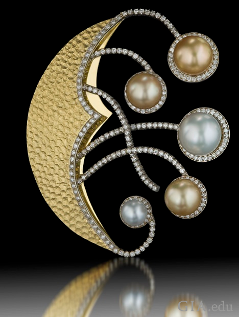 "A crescent moon-shaped pin with ""arms"" that reach out from its center. Each ""arm"" holds a pearl at the end."
