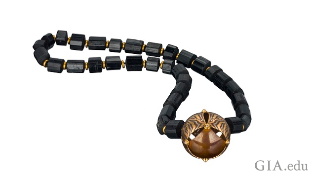 A mokume gane bead on a black gemstone necklace.