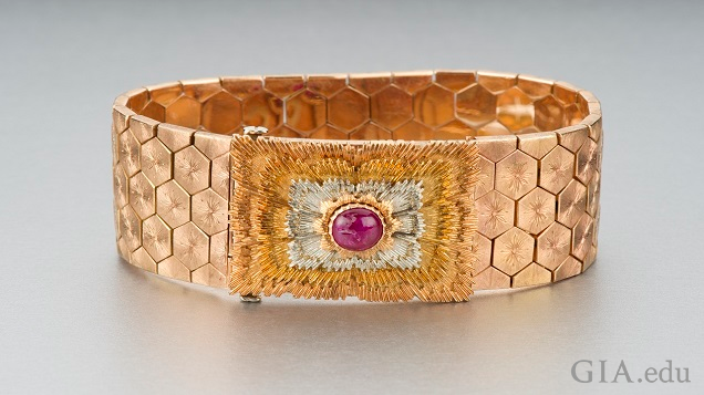 Wide rose gold patterned bracelet features a ruby cabochon.