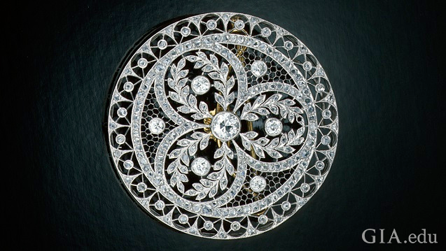 Circular pin with elaborate piercings and diamond embellishments.
