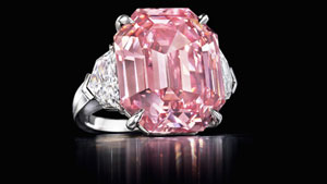 Pink diamond ring with two colorless diamonds on the side against a black background.
