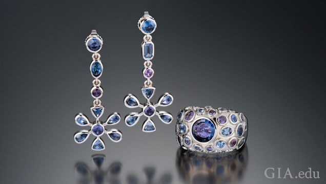 Earrings are flower-shaped and drop from a line of four blue and purple sapphires; the ring is domed-shaped with bezel-set blue and purple sapphires with a large blue centre stone.