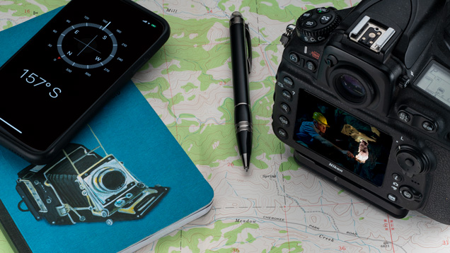 A notebook, pen, mobile phone with compass app and a digital camera sit on top of a map.